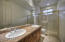 Guest bath with double sinks & glass enclosed shower.