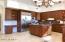 This kitchen features an island with prep sink, built-in fridge, separate wine fridge, breakfast nook & desk niche.