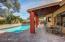 Covered patio overlooks glittering pool