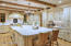 Spectacular details in the custom milled cabinets, enormous carrera marble island and beamed ceiling