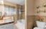 Bathroom has tub, tile shower surround and glass doors.