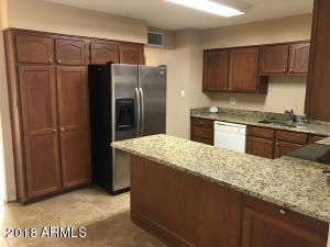 Gorgeous kitchen with granite counter top and large stainless steel refrigerator.