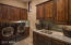 The laundry boasts granite counters, custom tile backsplash, sink, and generous solid alder cabinetry.