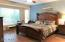 Master bedroom suite featuring a large bay window and accent painted wall.