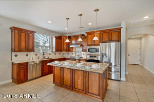 Custom gourmet kitchen was recently remodeled in 2018 with new cabinetry, granite countertops, under-mounted cabinet lights, and updated stainless steel appliances throughout.