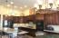 Kitchen with Custom Cabinets, Raw Edge Granite, Gas Cooktop and Wall Ovens
