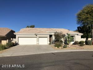 Welcome home - Pictured from across the street. View of 3 car garage and front yard with desert landscaping