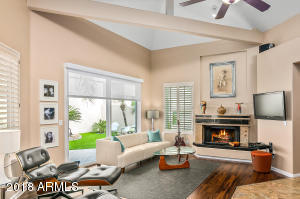 Great room features Brazillian pecan wood flooring, wood burning fireplace, vaulted ceiling, and plantation shutters.