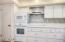 Pantry door left, wall microwave and oven with an electric cooktop & stainless steel hood.