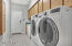 Large laundry room off garage with cabinets, counter space and built-in ironing board