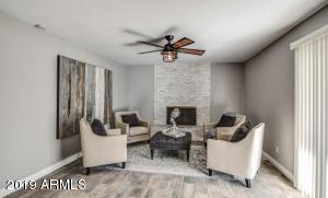 Formal living room with stone fireplace & outlet for your tv