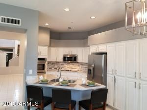 Kitchen: Quartz counters, newer SS appliances & tile backsplash
