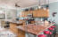 Kitchen area has plenty of cabinet storage, and room for four at the bar. Island has extended countertop for extra space.