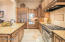 Six burner Wolf range with griddle, vegetable sink with disposal, warming drawer, and appliance garage make this kitchen a chef's dream