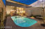 Rear elevation at night as pool and interior sparkle with light.