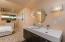 New double sink vanity and custom lighting in guest suite.