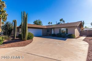 Pretty ranch with beautiful mature desertscape and an extra wide driveway leading to the two car garage.