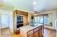 Kitchen features built in oven, island, granite counter tops, and plenty of cabinet storage space.