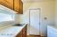 Large laundry room, located off of the kitchen. Huge built-in cabinets offer even more storage + lots of counter space. Room is light and bright, thanks to the large window. Room also offers access from the garage, directly into the home.