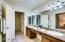 Master bathroom features dual sinks,a vanity area + a walk in closet.