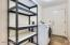 Large laundry room with shelving and washer/dryer included.