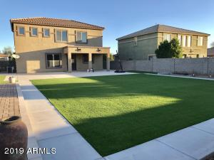 Large backyard is low maintenance with synthetic turf and plenty of patio spaces