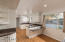 Custom kitchen features foil-finish cabinetry, granite slab counters, breakfast bar + eat-in area