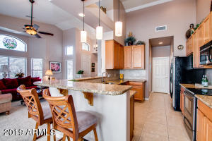 Chef's Kitchen with custom backsplash, granite countertops, breakfast bar, stainless steel appliances, smooth-top cooktop, upgraded cabinetry and lighting with a large pantry!