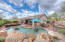 Another view of this oversized and gorgeous backyard, pool, rock waterfall and multiple entertaining areas!