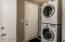 Laundry room with stacked washer/dryer and door to side yard.