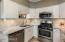 White cabinets, carrera marble counters, double basin sink, stainless steel appliances.