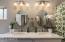 Dual vanity sink and storage cabinets below.