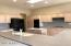 Spacious kitchen with skylight, lots of cabinets, grey Corian cabinets with integrated sink, black appliances, pantry & kitchen island.