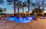 Twilight view of pool, spa, cascading boulder waterfall and from the kiva fireplace and BBQ area of home looking South.
