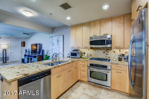 Gorgeous 2 bedroom + den/study, 2 bath, 1319Sqft Optima Camelview Condominium. Breathtaking kitchen includes granite countertops, rich cabinetry and stainless steel upgraded appliances. Beautiful travertine flooring throughout all living areas/baths and high end carpet in the bedrooms. Spacious luxurious landscaped 1100 SqFt terrace provides a relaxing space or wonderful entertaining area! This must see unit will not last long!!! . All found within the luxurious Optima Camelview. Fitness center, indoor/outdoor pools+spas, steam rooms, basketball/racquetball/putting-green, concierge, restaurants+ so much more!