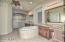 Dual sinks, separate tub, granite counters, framed mirrors, and large walk-in shower with tile surround