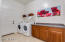 Spacious laundry room includes cabinets and countertop for convenience and fantastic storage