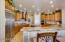 Kitchen with large walk in pantry, custom frameless Knotty Elder cabinetry in two tone scheme
