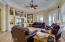 Great room with beautiful ceiling fan and can lighting in octagon ceiling with crown molding