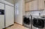 Large expansive laundry room complete with 2nd refrigerator and plenty of cabinetry, a laundry sink and hanging space for clothes above.