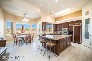 Neutral kitchen with rich cabinets, granite counters and gas stove.