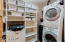 LAUNDRY ROOM FEATURES STACKED FRONT LOADING WASHER AND DRYER AND LTOS OF EXTRA STORAGE.