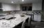 This large kitchen is high lighted by custom cabinets, main sink and prep sink, and a huge island.
