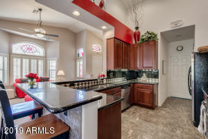 Chef's Kitchen with granite counter tops, stainless steel appliances, custom backsplash, upgraded cabinetry and lighting.