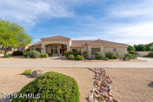 Front of Home w/ circular drive, low maintenance desert landscape, electric RV gate with motor court.