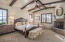 The master bedroom features vaulted ceiling with wood beams, cantera stone fireplace, and door to the back patio