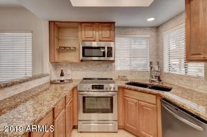 Beautifully upgraded kitchen with all new back splash and a modern open-faced cabinet with glass shelves