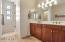 Walk-in tiled shower and dual sink vanity hall bathroom