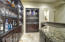 Custom built wet bar with Tropic Brown granite stone counter top, Alder wood cabinets with lighted glass shelving and built in under-counter wine refrigerator.