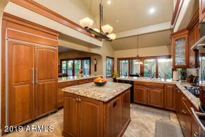 Kitchen with vaulted ceilings, double ovens, built in fridge, and granite counters
